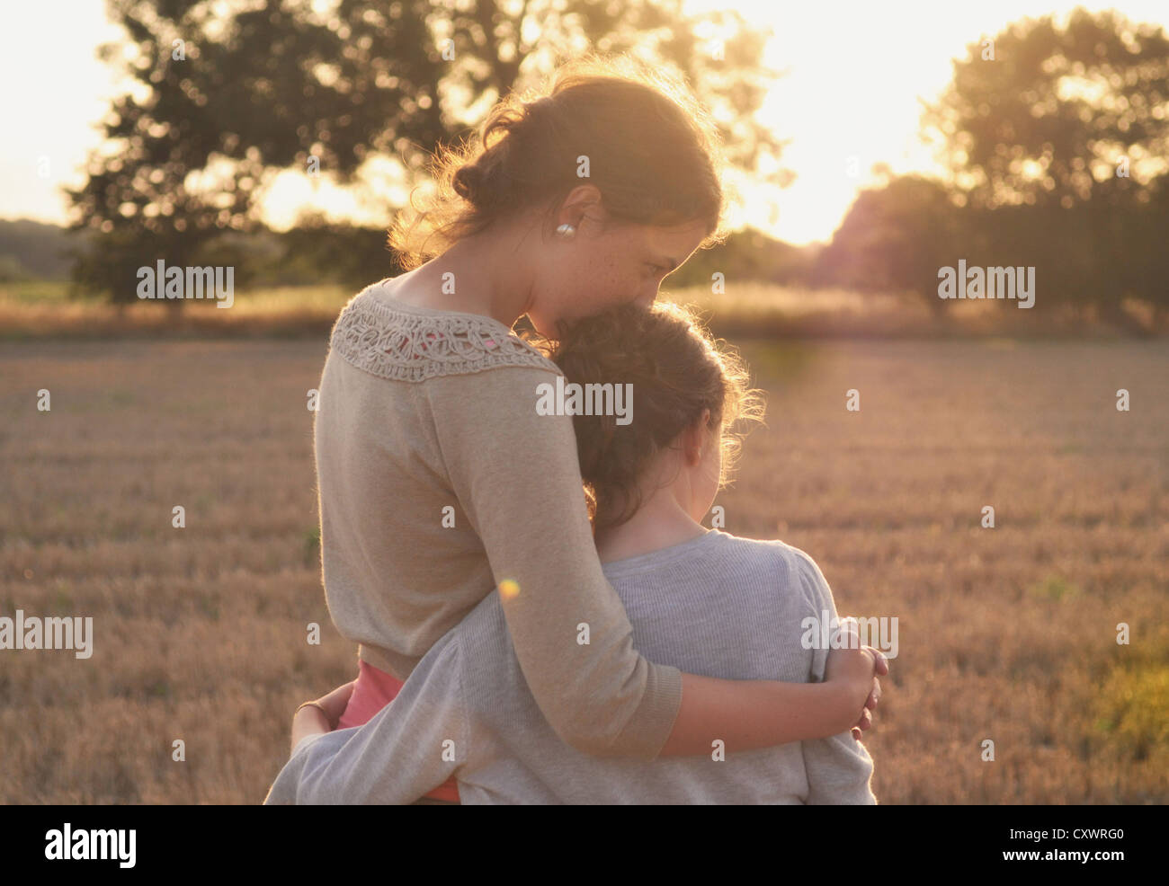 Mother and daughter hugging in field - Stock Image