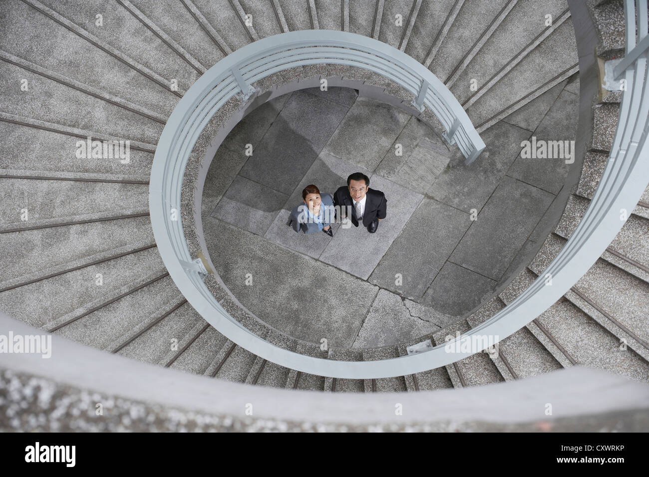 Business people under spiral staircase - Stock Image