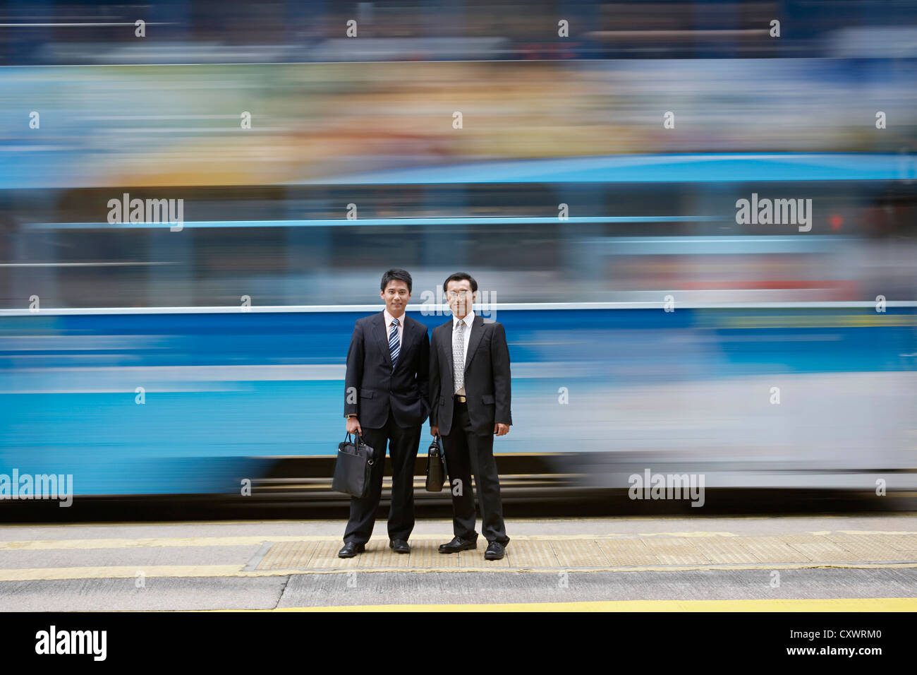 Businessmen standing by blurred bus - Stock Image