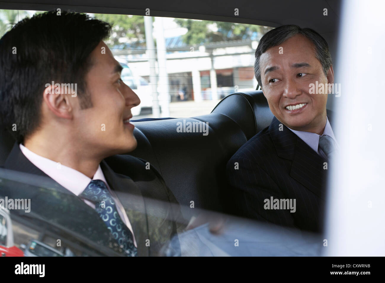 Businessmen riding together in taxi - Stock Image