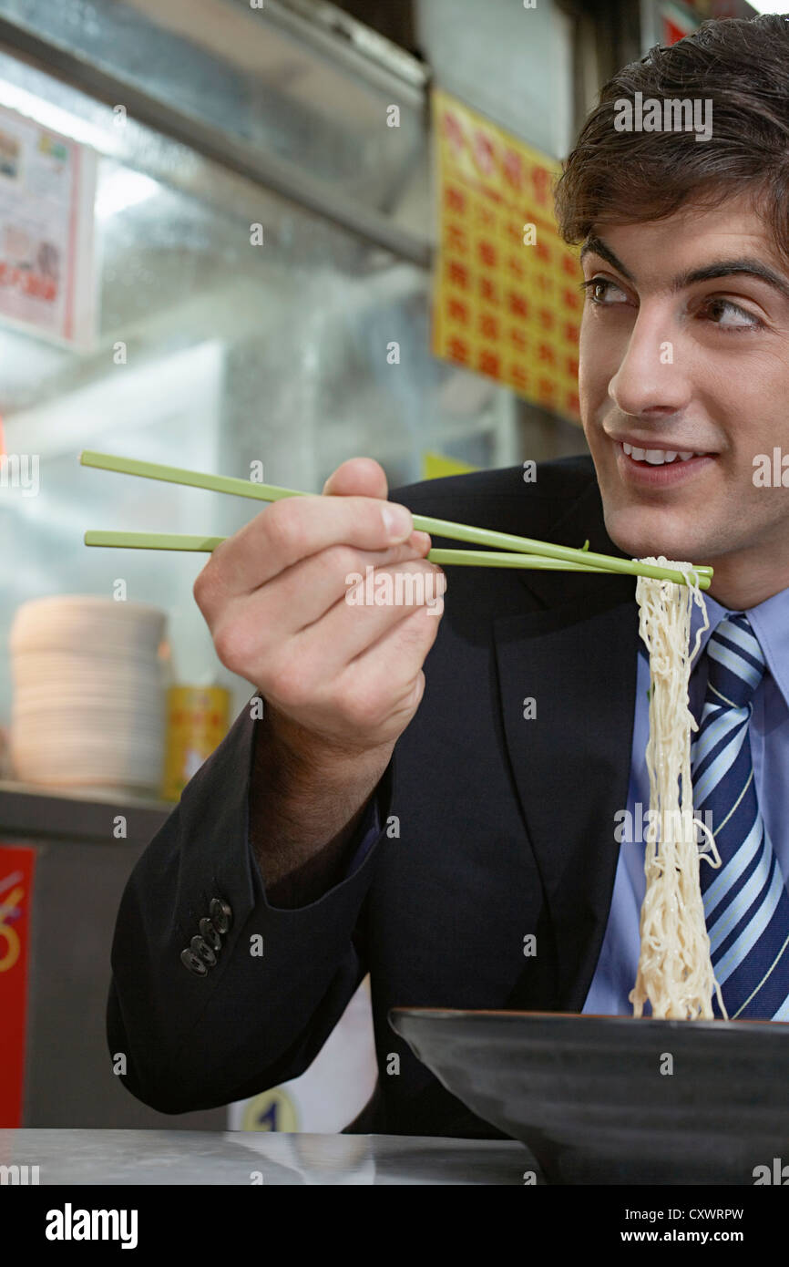 Businessman eating noodles in cafe Stock Photo