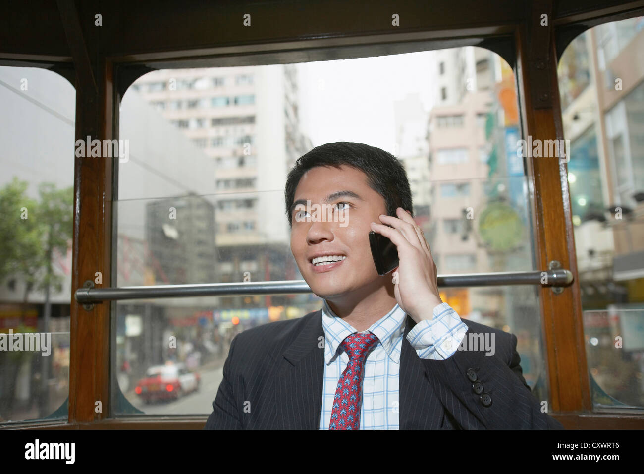 Businessman on cell phone on bus - Stock Image