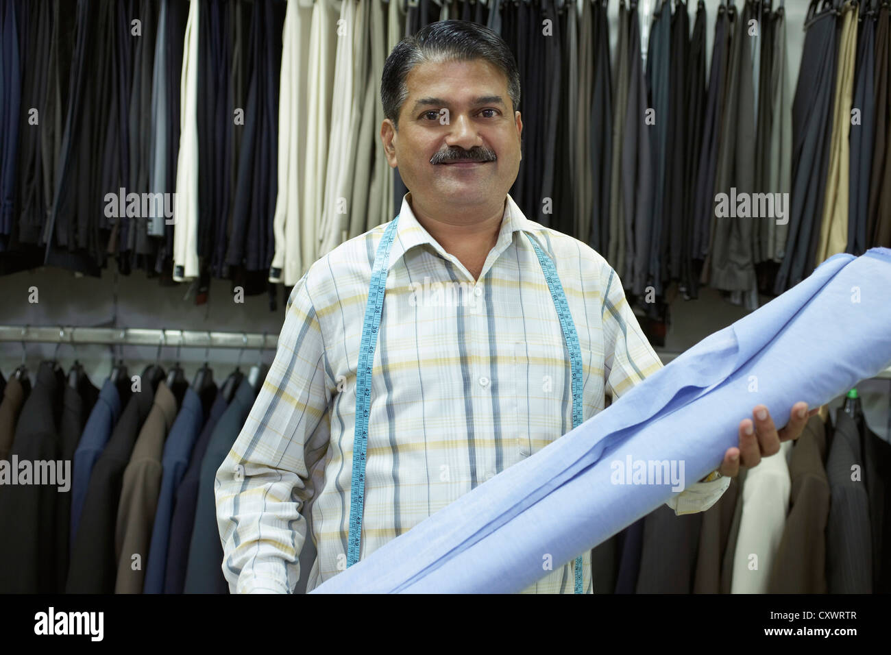 Tailor holding fabric in shop - Stock Image
