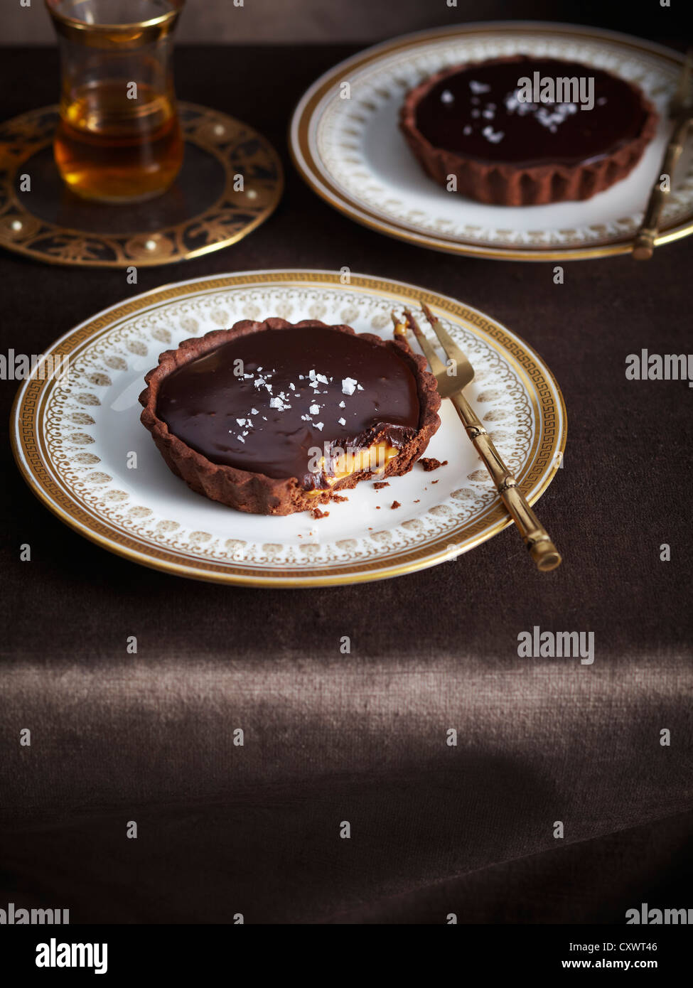 Plate of salted chocolate caramel tart - Stock Image