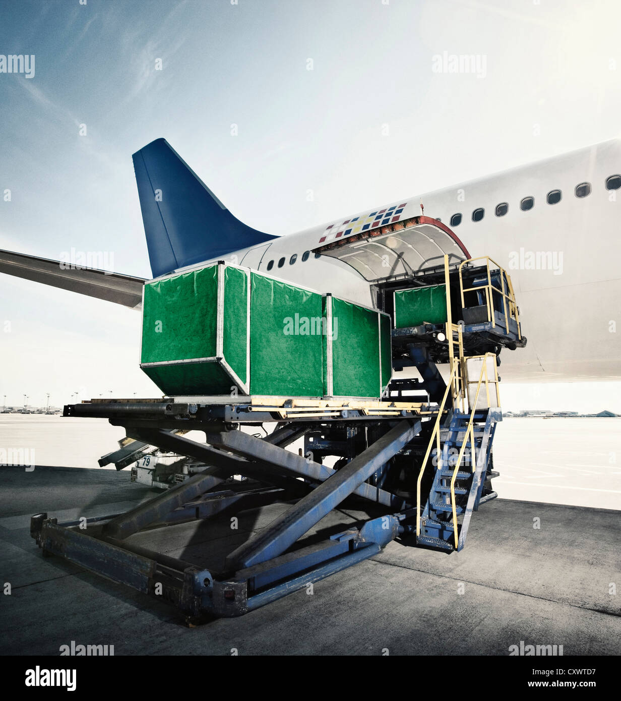 Green boxes loading into airplane - Stock Image