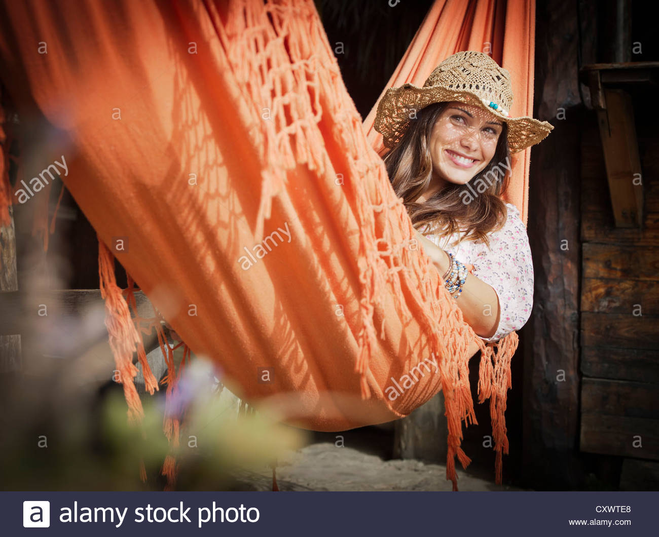Woman in sunhat relaxing in hammock - Stock Image