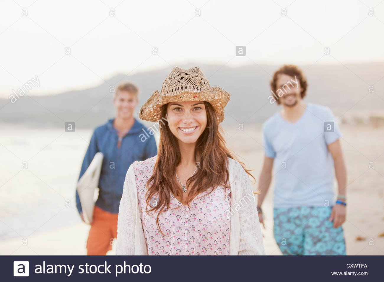Friends walking together on beach - Stock Image