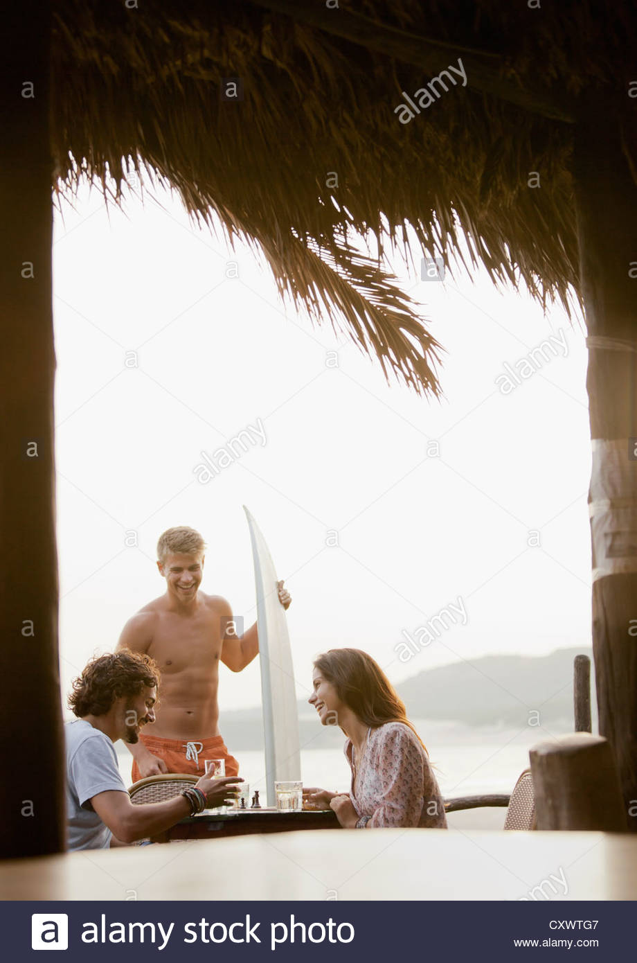 Friends having drinks in tropical bar - Stock Image