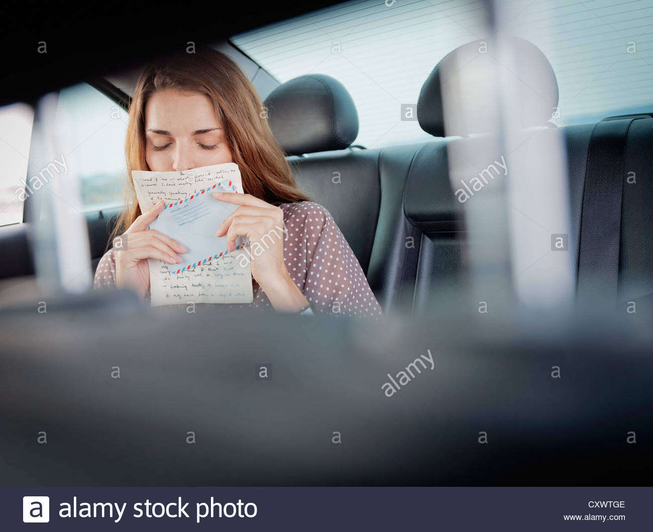 Woman kissing letter in backseat of car Stock Photo