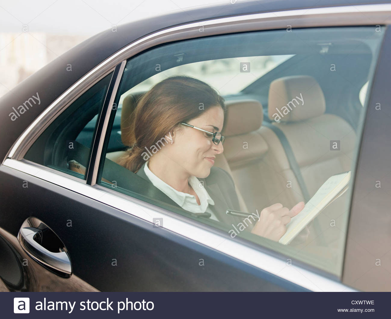 Businesswoman writing in backseat of car - Stock Image