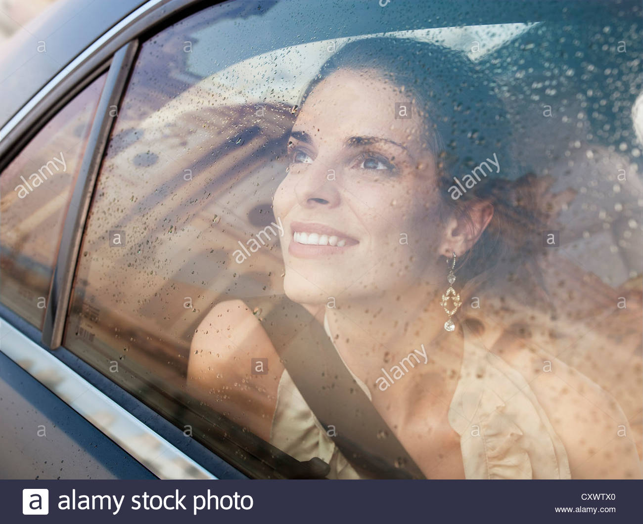 Smiling woman looking out car window - Stock Image