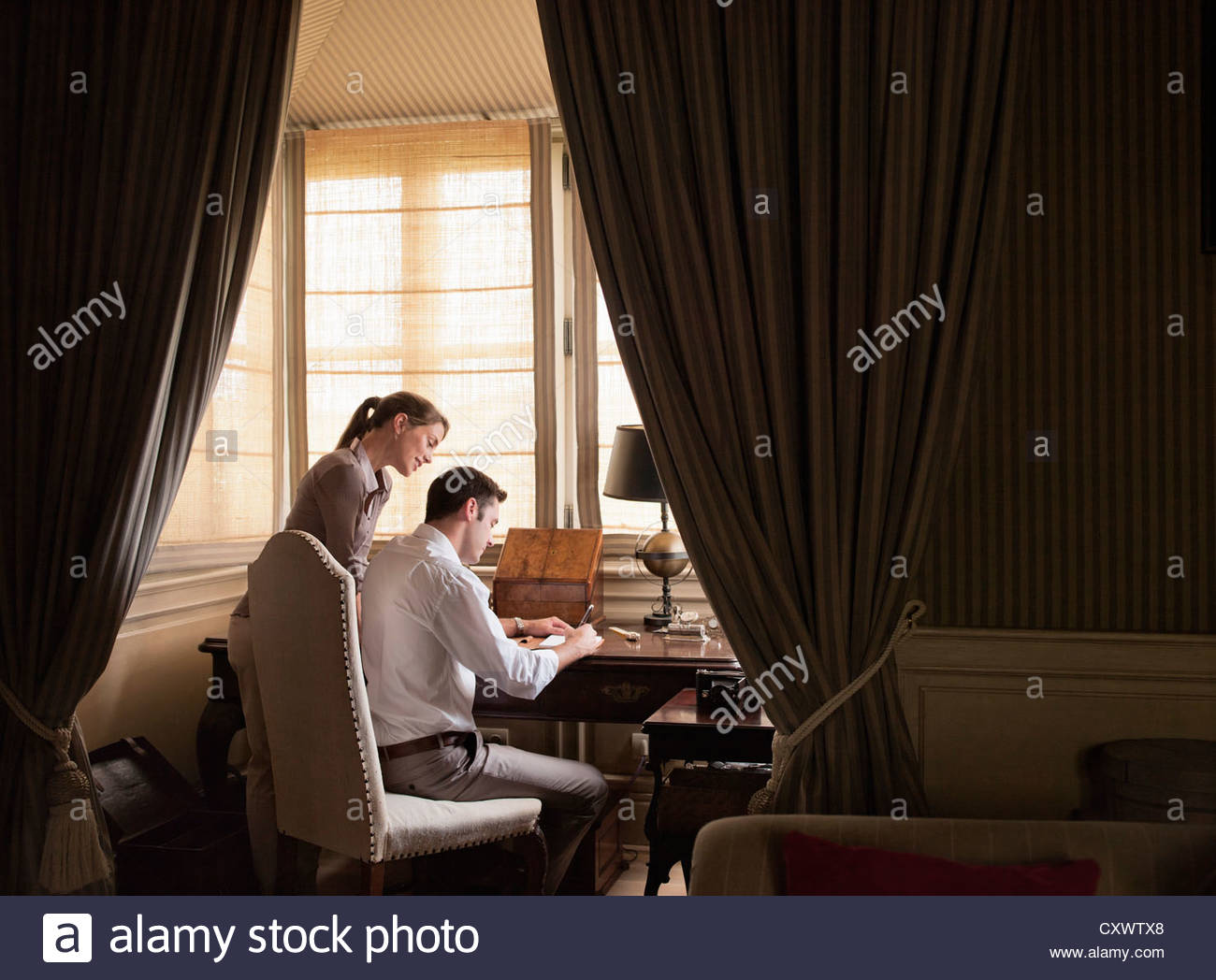 Couple writing at desk in study Stock Photo