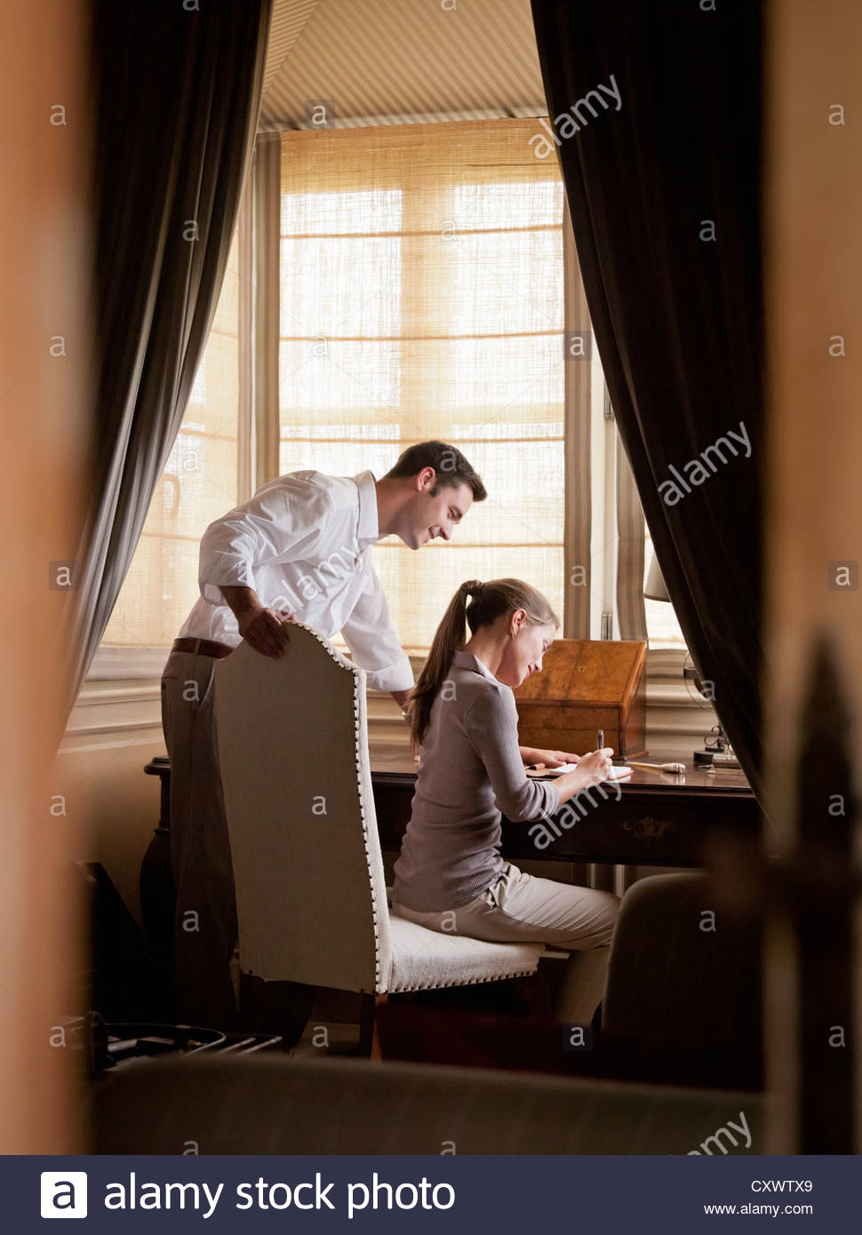 Couple writing at desk in study - Stock Image
