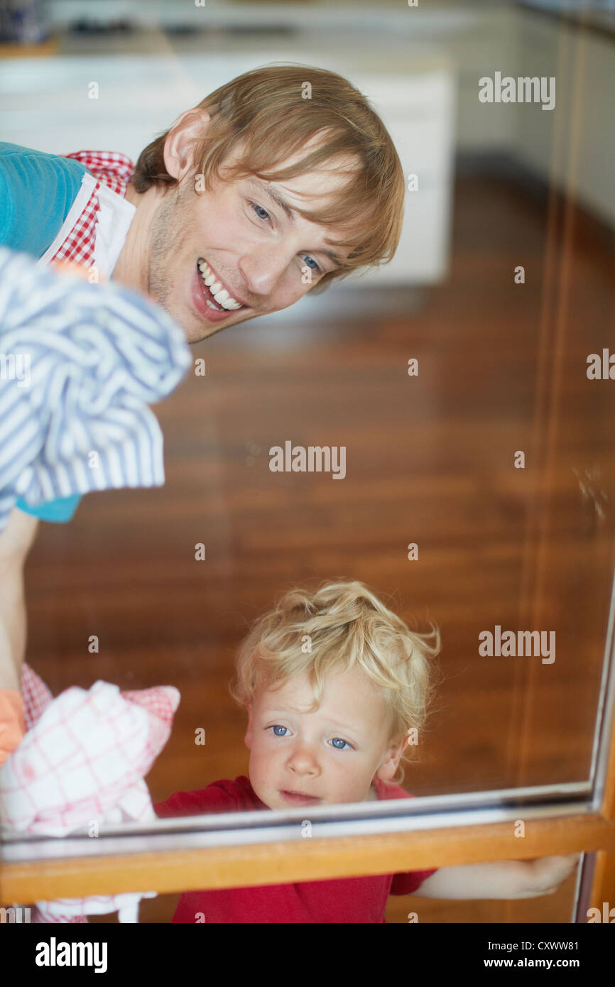 Father and son washing windows - Stock Image
