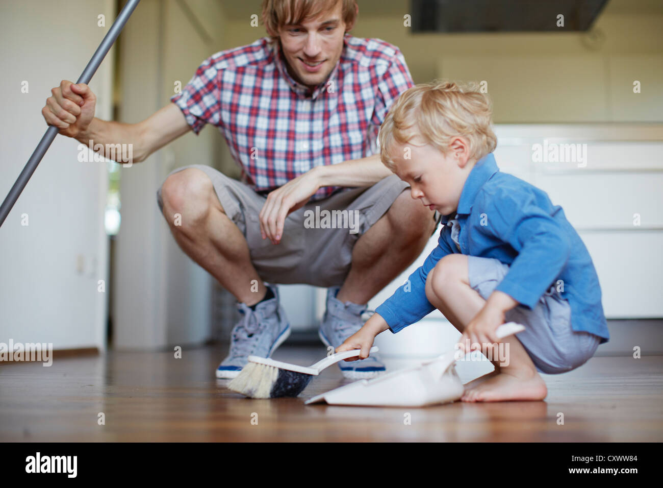 Boy helping father sweep floor - Stock Image