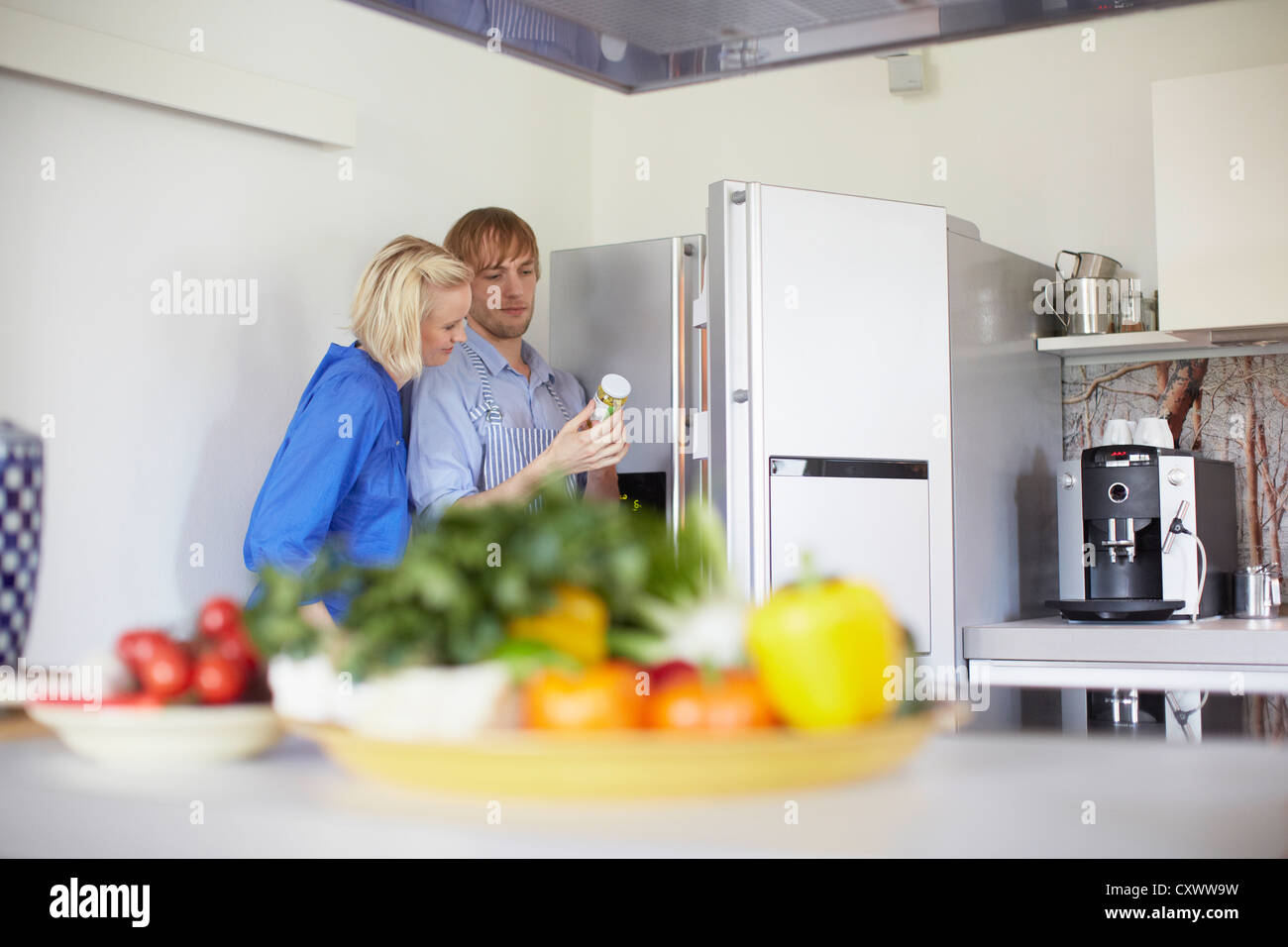 Couple cooking together in kitchen - Stock Image
