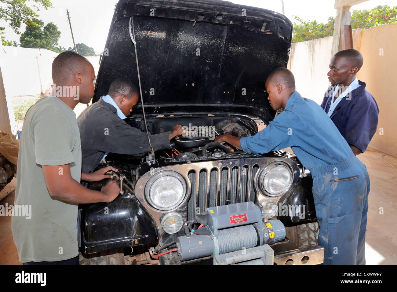young mechanics works on a car engine. Machui Vocational Center, Machui, Zanzibar, Tanzania Stock Photo