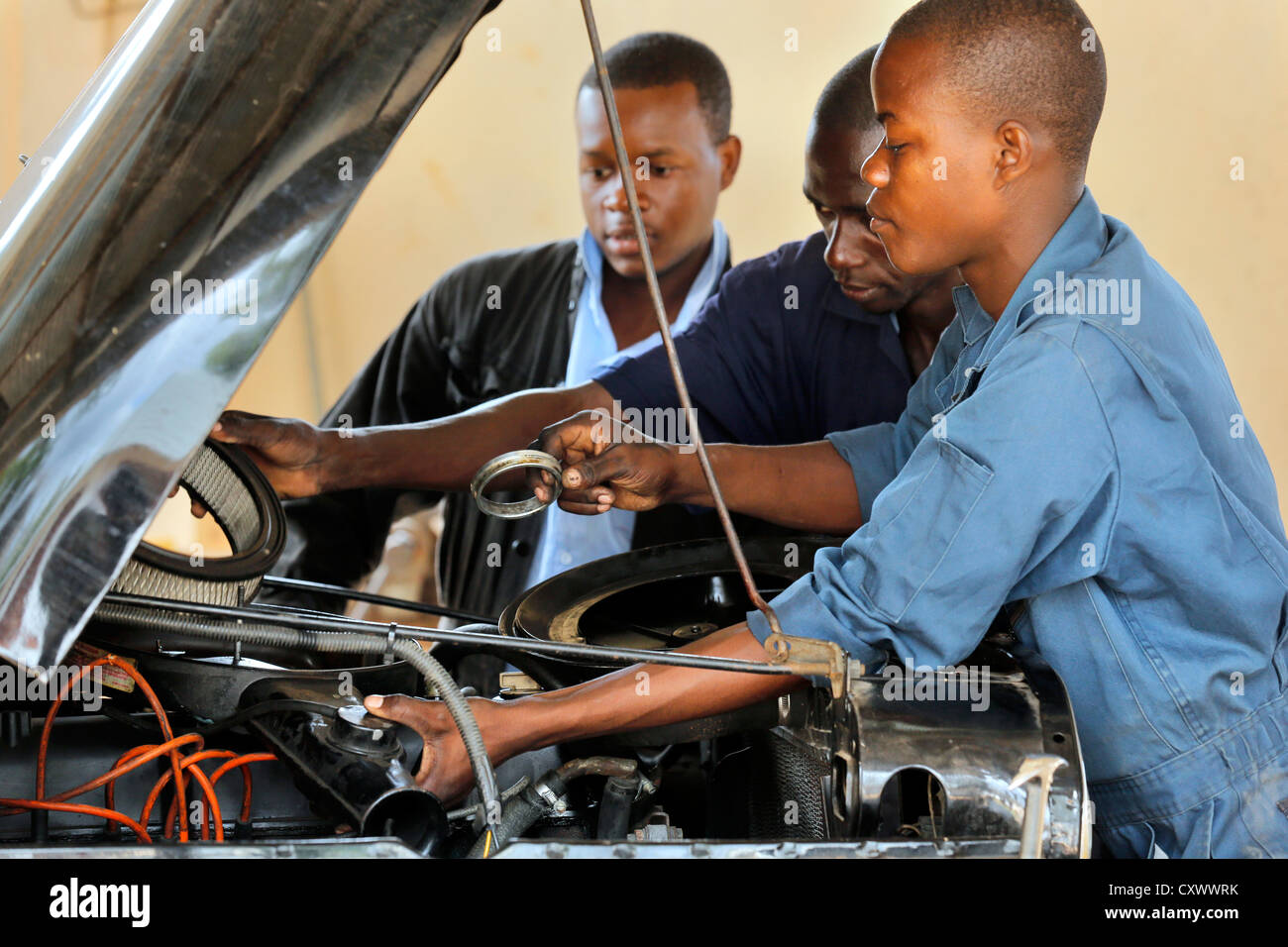 young mechanics works on a car engine. Machui Vocational Center, Machui, Zanzibar, Tanzania - Stock Image