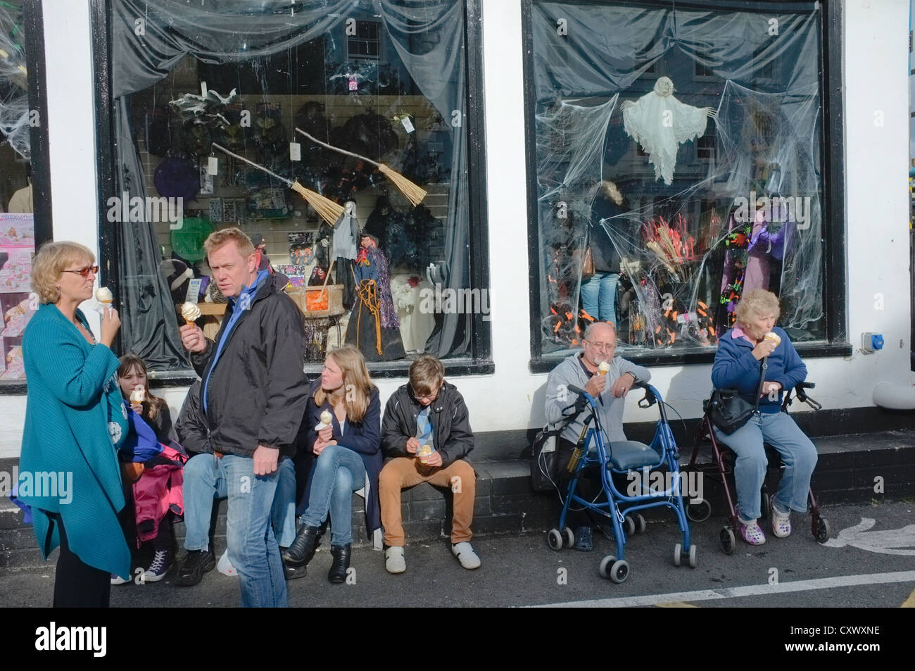 People eating ice creams in Falmouth, Cornwall, UK during unseasonably warm weather in October. Halloween decorations - Stock Image