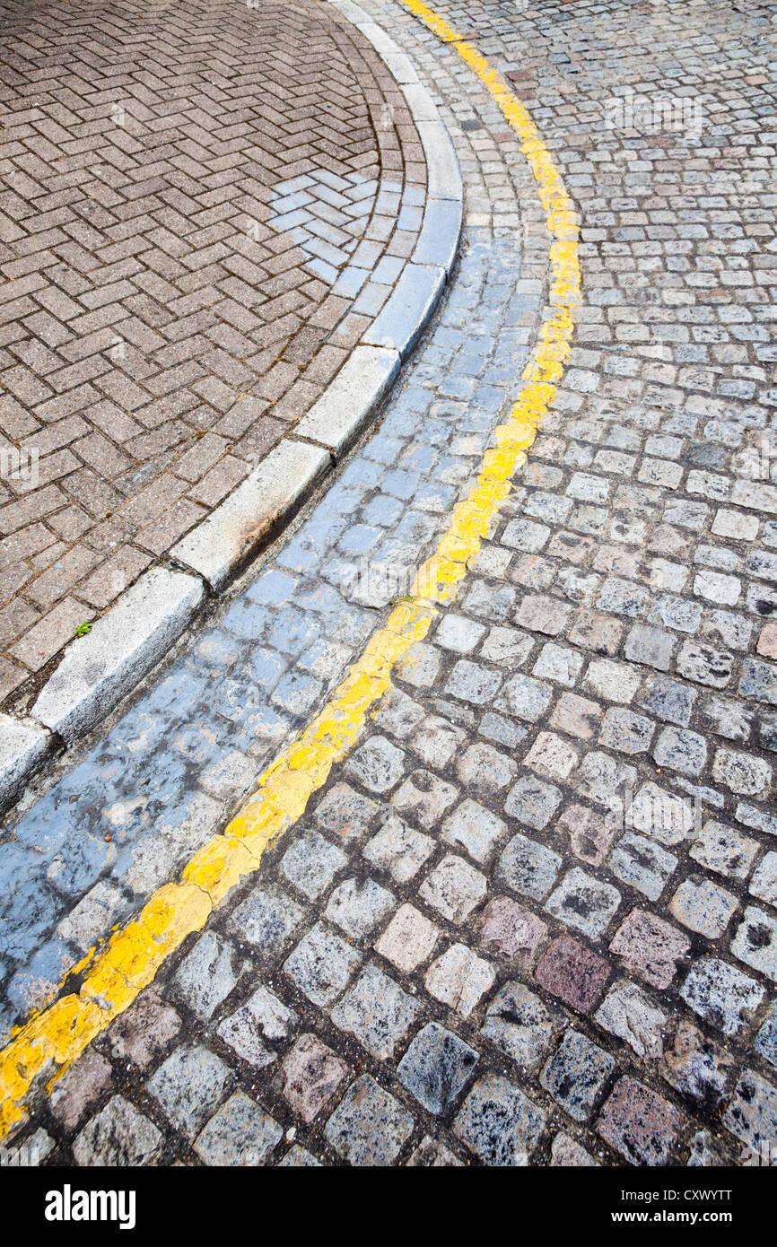 Yellow line road markings on cobbled street corner kerb, UK - Stock Image