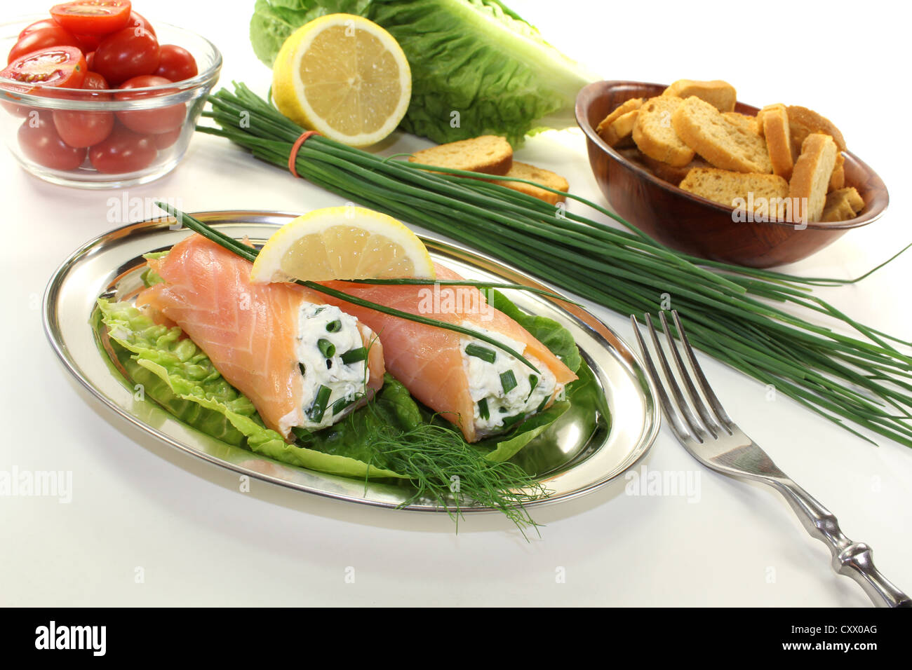 smoked salmon rolls with cream cheese, chives and a lemon slice - Stock Image