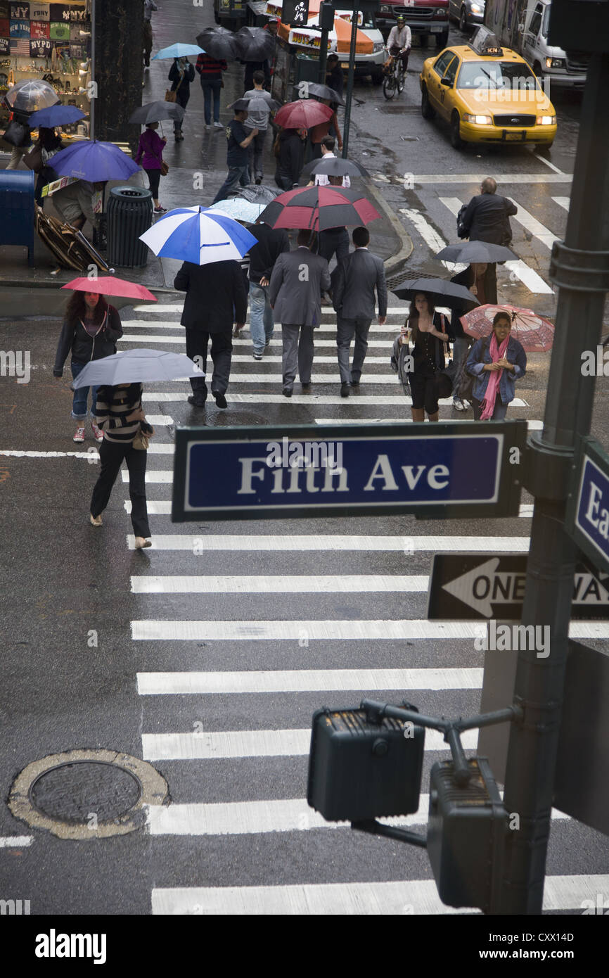 Umbrellas up on a rainy day on 5th Avenue and 46th Street in New York City. - Stock Image