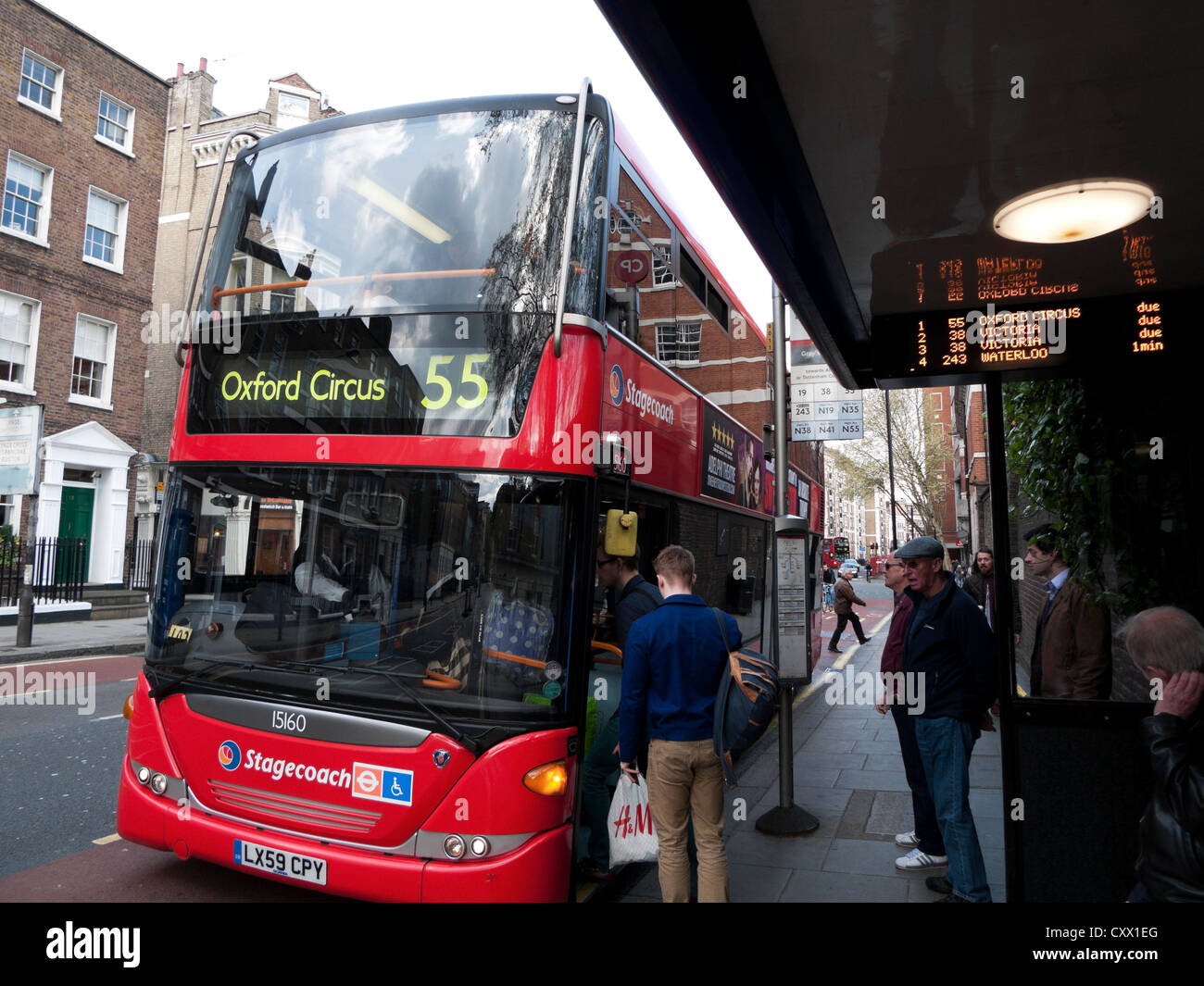 People boarding a 55 red double decker bus destined for Oxford Circus London England UK KATHY DEWITT - Stock Image