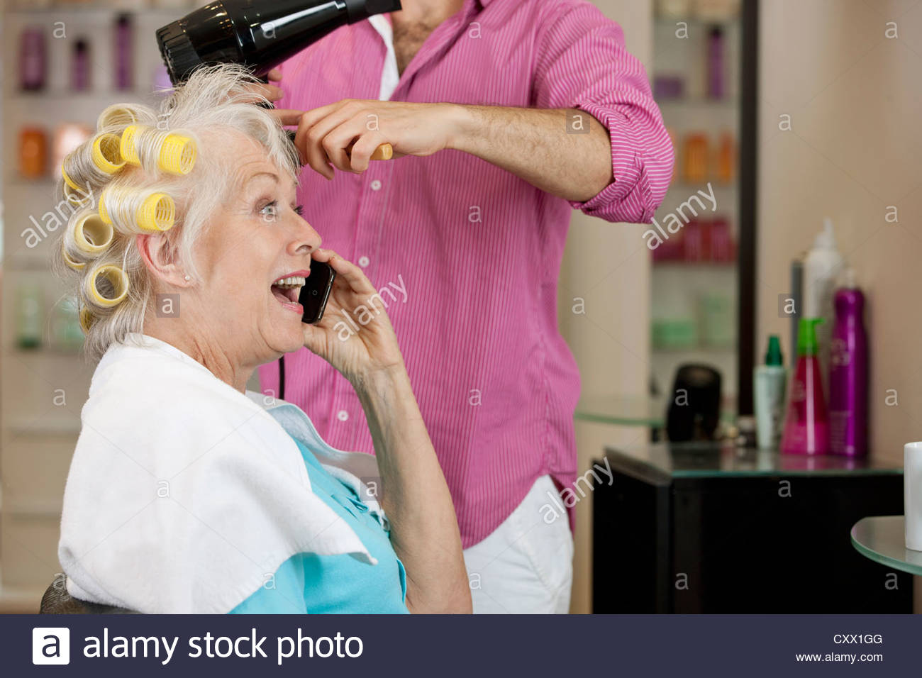 A senior woman talking on a mobile phone whilst having her hair dried - Stock Image