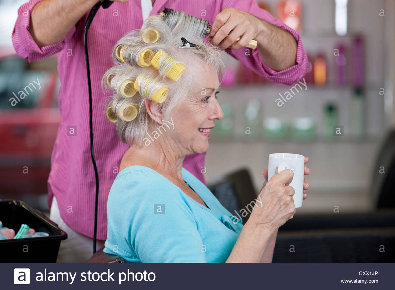 A senior woman drinking a hot beverage whilst having her hair dried, close up - Stock Image