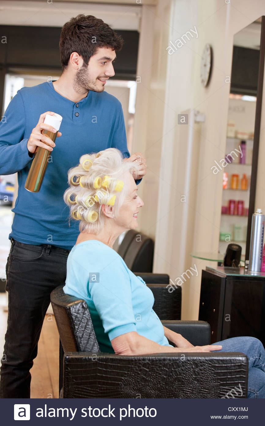 A male hairdresser applying hairspray to a female clients hair - Stock Image