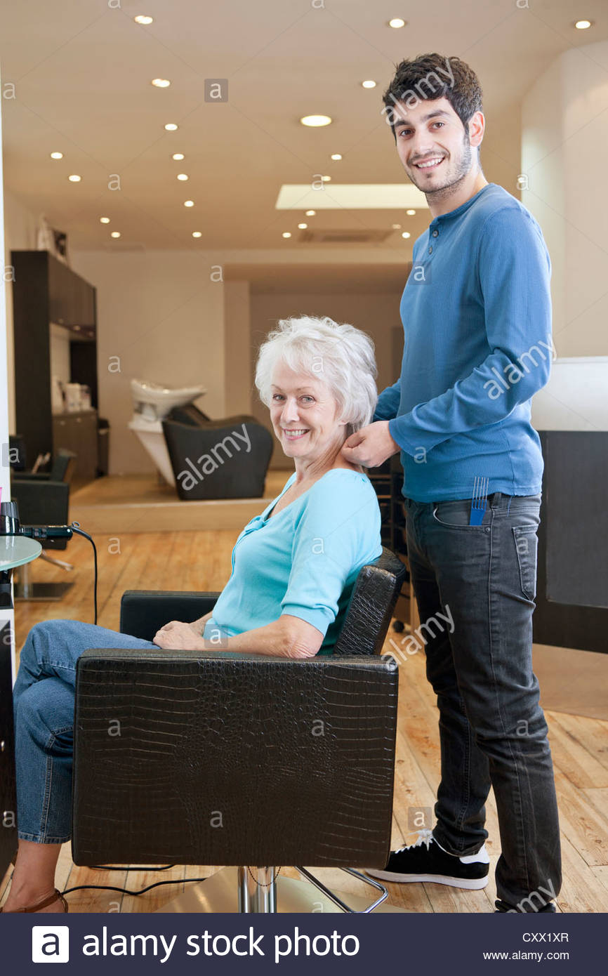 A male hairdresser and female client in a hairdressing salon - Stock Image
