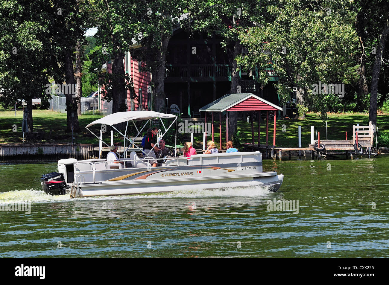 Pontoon boat with mixed group of people cruising the Fox River in Northern Illinois. - Stock Image