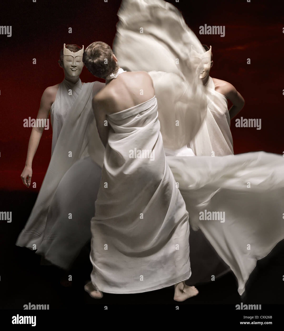 Dancers in flowing gowns perform under dramatic lighting amid a black backdrop - Stock Image