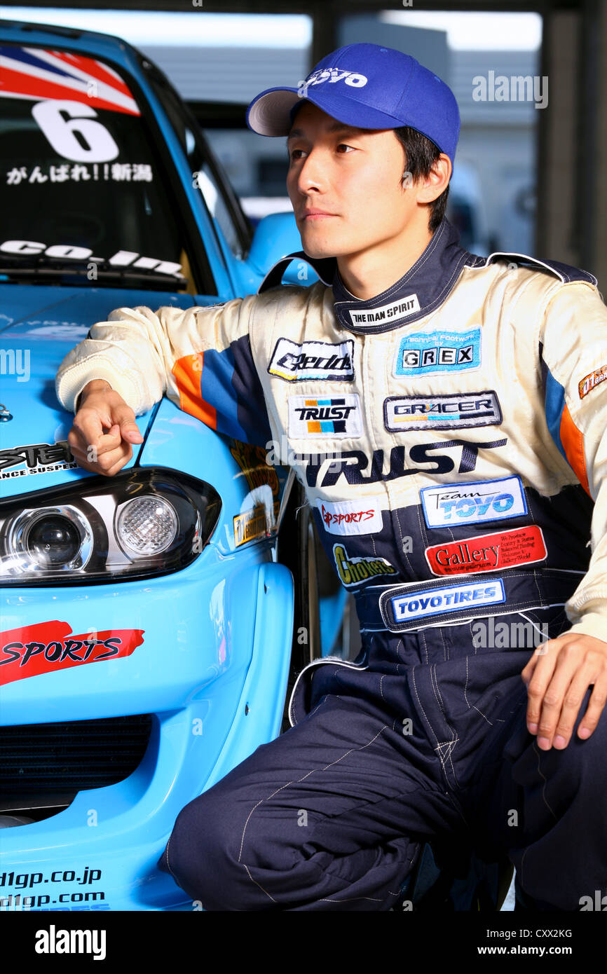 Portrait of race driver posed with car in garage - Stock Image