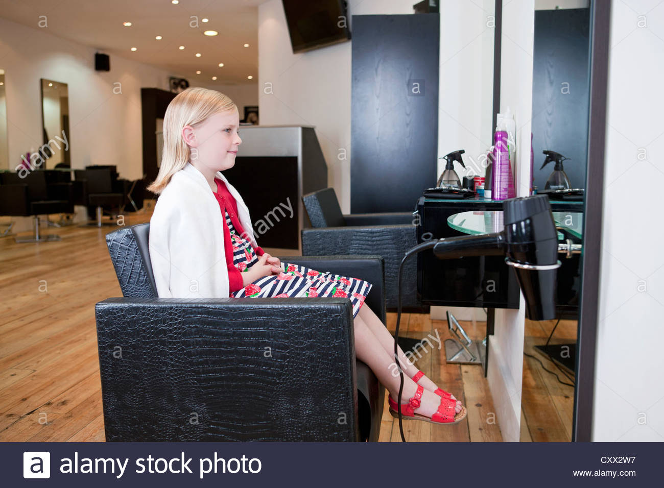 A young girl looking in a mirror at a hairdressing salon - Stock Image