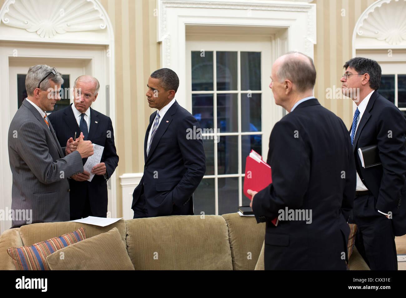 US President Barack Obama and Vice President Joe Biden talk with senior advisors September 11, 2012 in the Oval - Stock Image