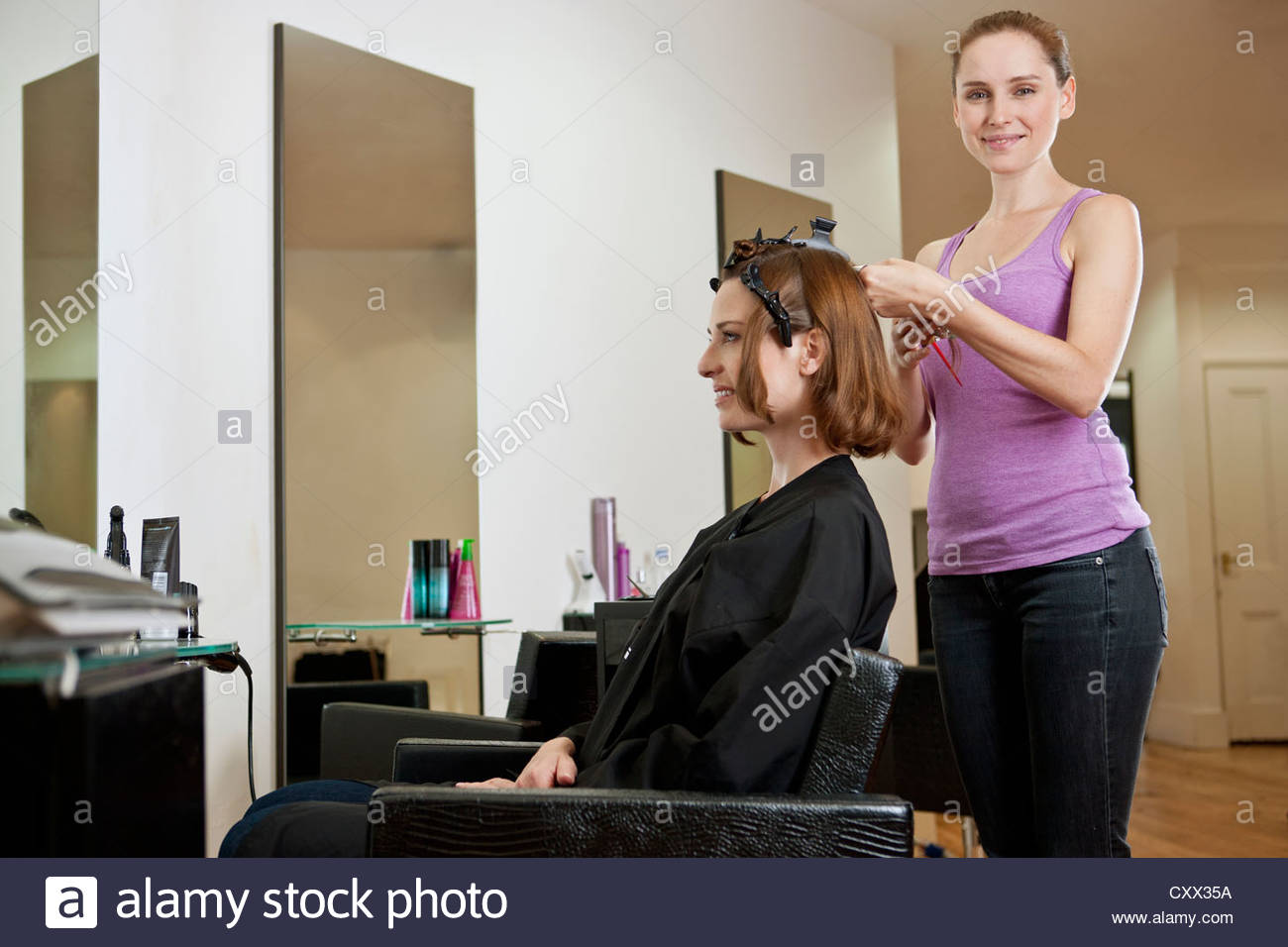 A female hairdresser colouring a female clients hair, smiling to camera - Stock Image