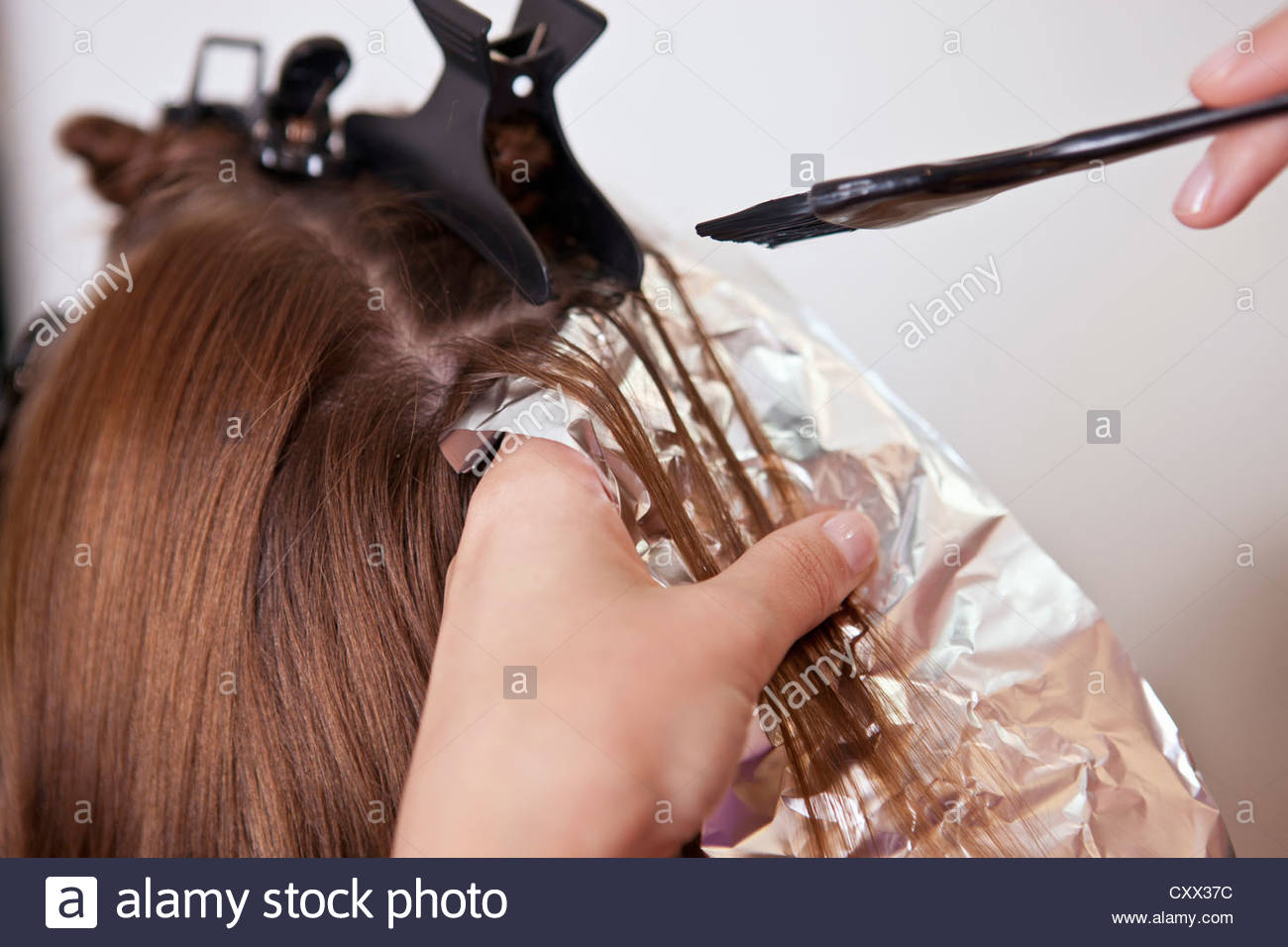 A female client having her hair coloured in a hairdressing salon, close up - Stock Image