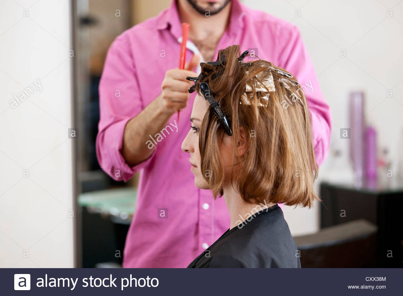 A hairdresser putting foils in a female clients hair - Stock Image