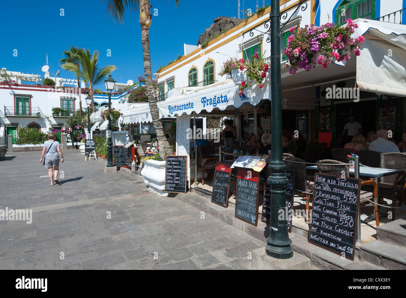 Restaurants and cafes on the harbour front at Puerto Mogan Gran Canaria Canary Islands Spain with menus outside - Stock Image