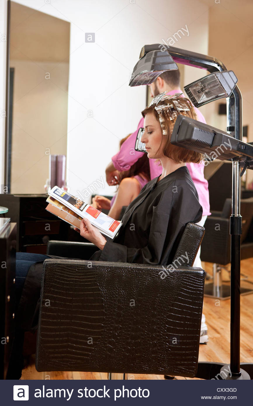 A female client reading a magazine whilst she has her hair coloured in a hairdressing salon - Stock Image