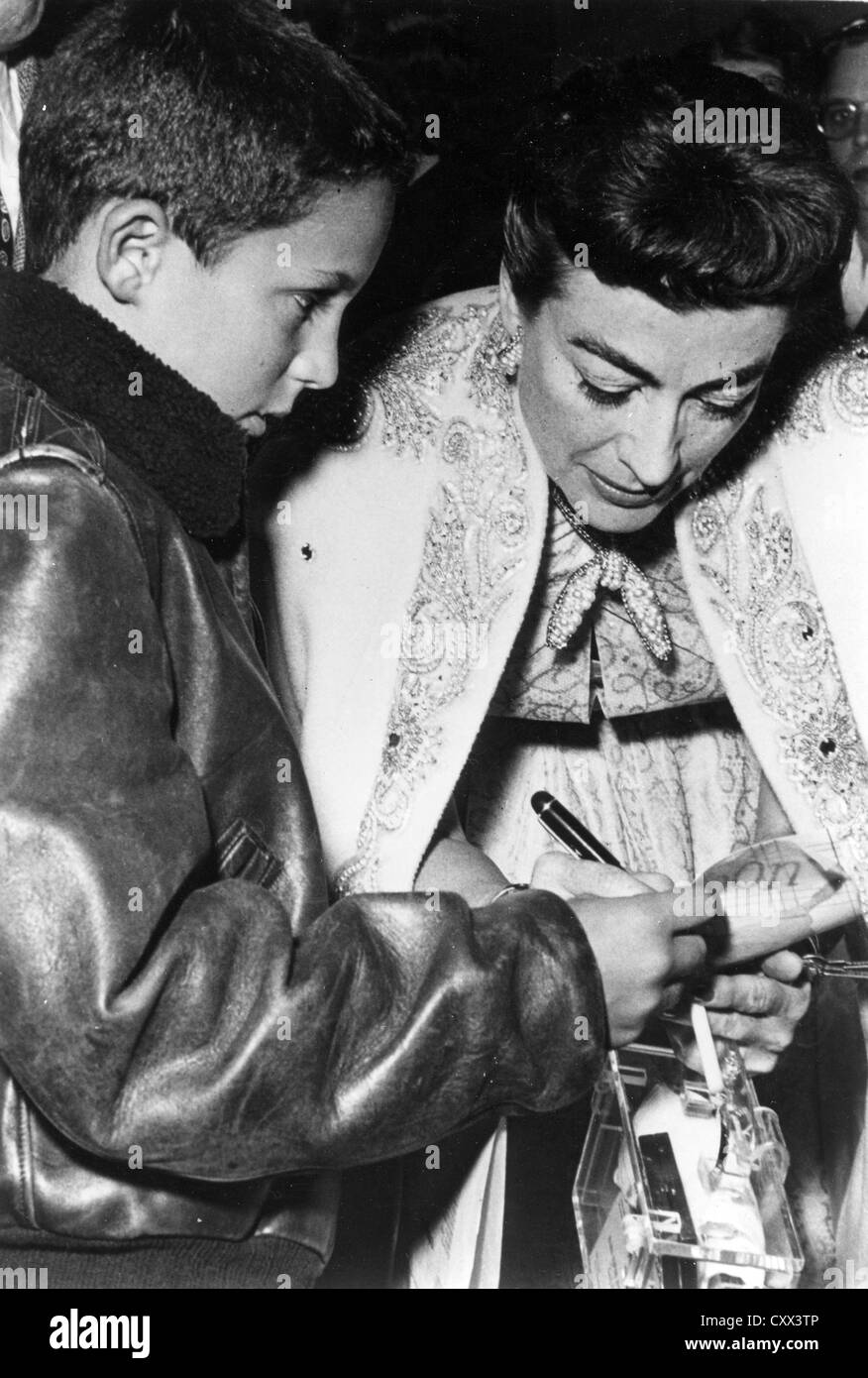 JOAN CRAWFORD (1905-1977) US film star signs her autograph for a young fan about 1970 - Stock Image