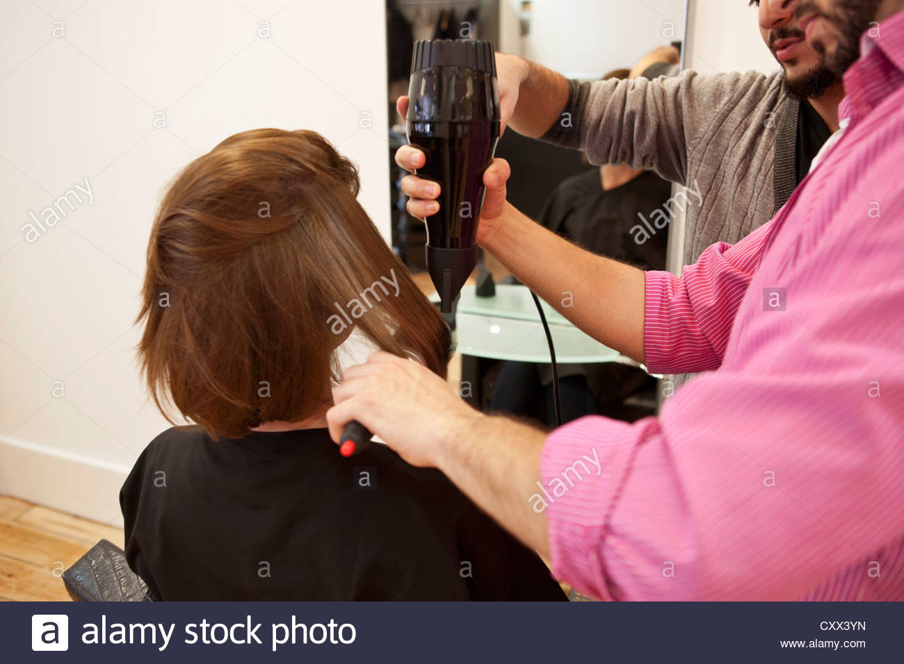 A female client having a blow dry in a hairdressing salon - Stock Image