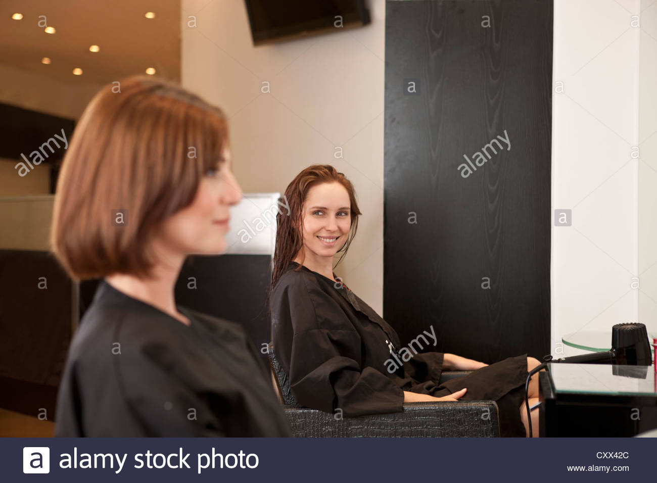 Two female clients sitting in a hairdressing salon - Stock Image
