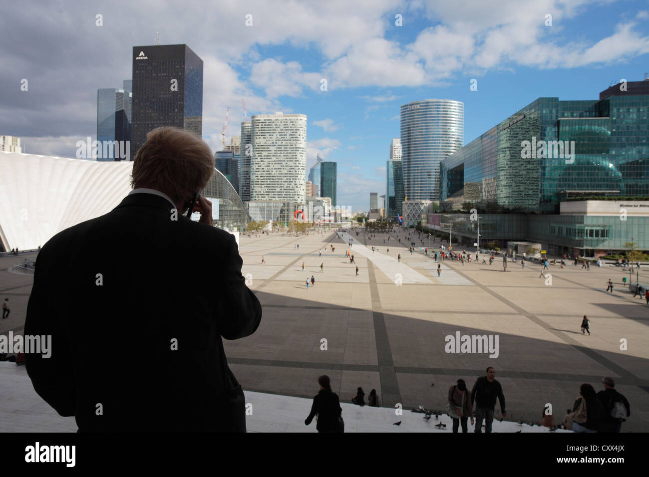 businessman with mobile phone on stairs of La Grande Arche with view to the towers of the financial district La - Stock Image