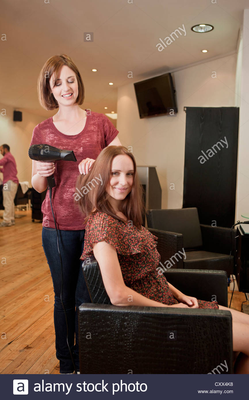 A female hairdresser blow drying her female clients hair - Stock Image