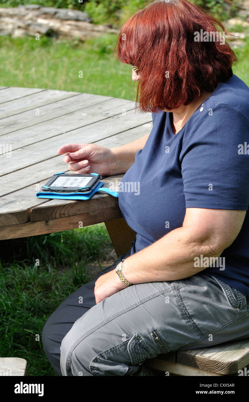 Woman sat at wood table, reads Kindle e-book, set to large font, - Stock Image