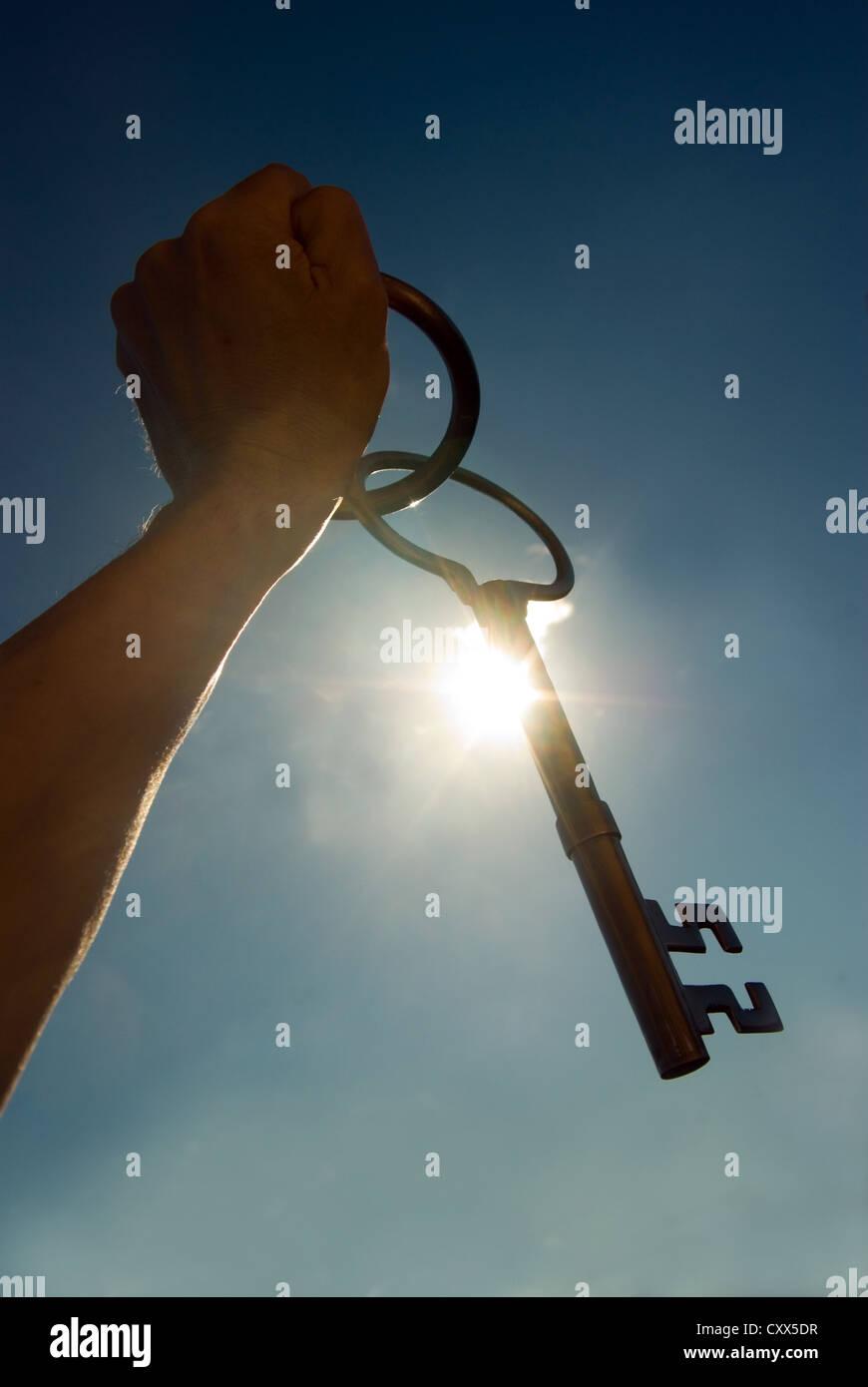 Hand Holding up large key.Freedom / Escape concept - Stock Image
