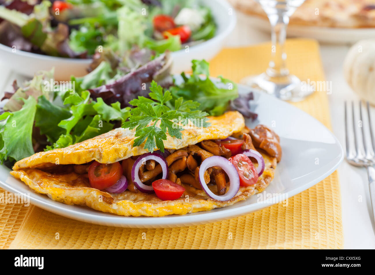 Omelet filled with chanterelle mushrooms and vegetable salad - Stock Image