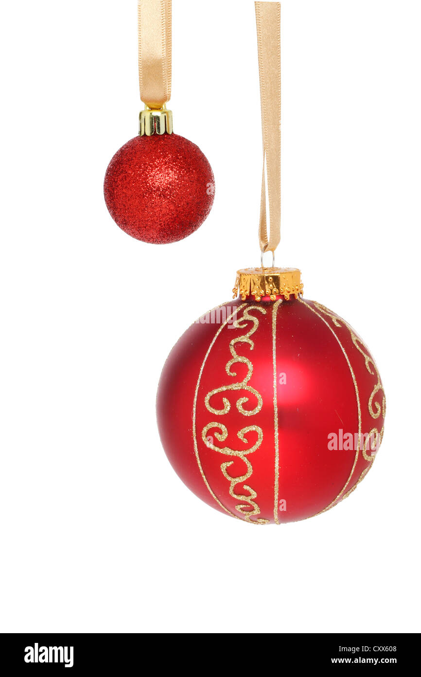 ccbd464e093f Large and small red Christmas baubles hanging from gold ribbons isolated  against white - Stock Image